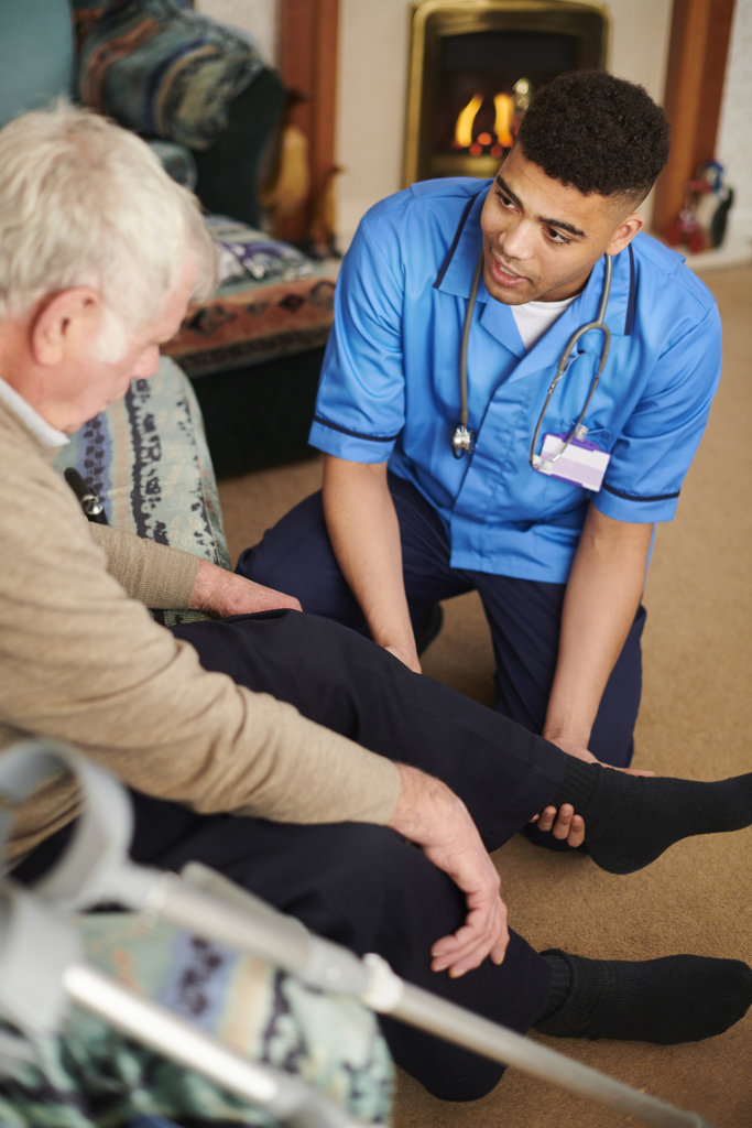 Senior man with care worker at home exercising the new knee joint